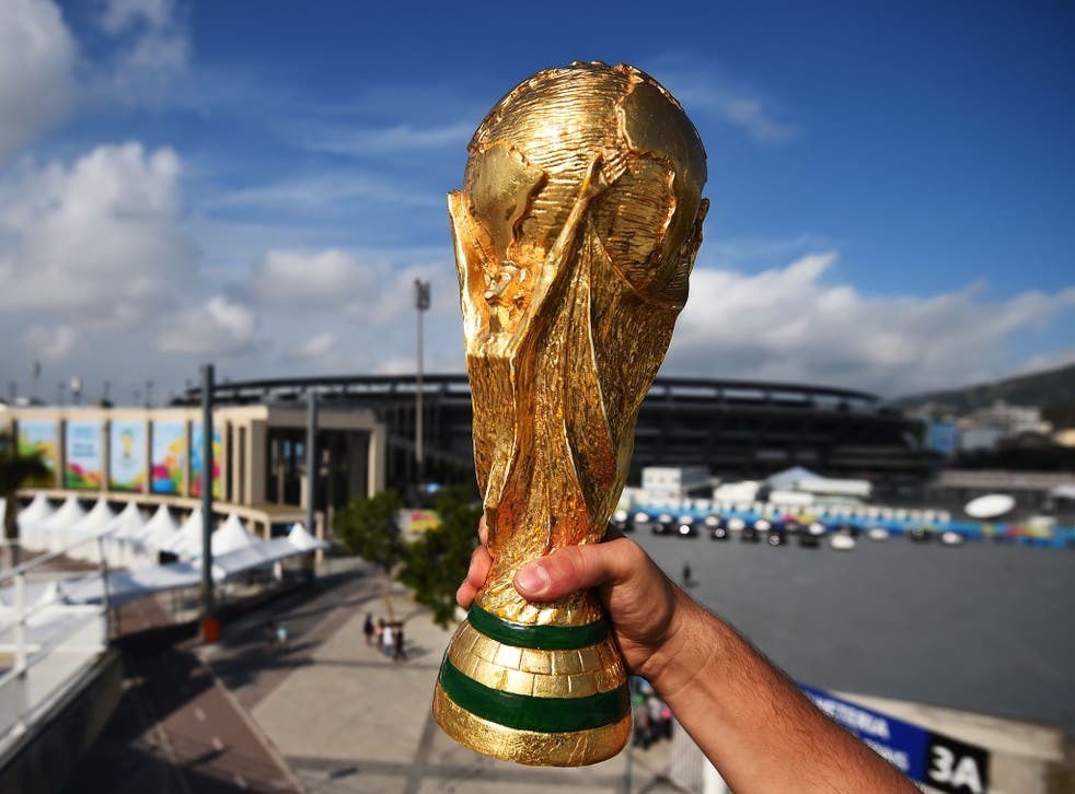 A fan holds a replica of the World Cup Trophy near the Maracana Stadium