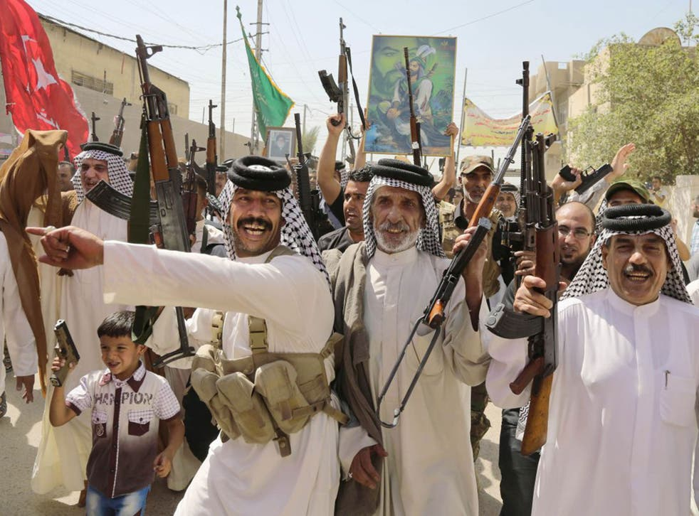 Iraqi Shia fighters chant slogans against the al-Qa'ida-inspired Islamic State of Iraq and the Levant in Baghdad's Sadr City