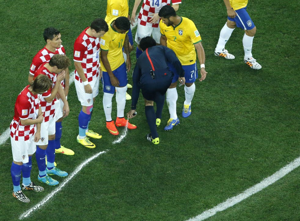 Japanese referee Yuichi Nishimura sprays a line after calling for a free kick for Brazil