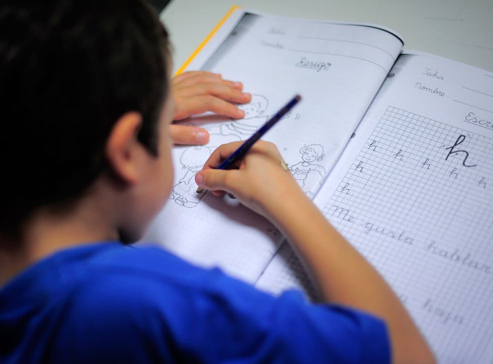 A young boy from a financially troubled family does his homework at the care centre Marti-Codolar in Barcelona on November 21, 2012 where he spends his afternoons with other children. Children from many families brought close to poverty by Spain's economic crisis benefit from free care services such as this free evening learning centre.