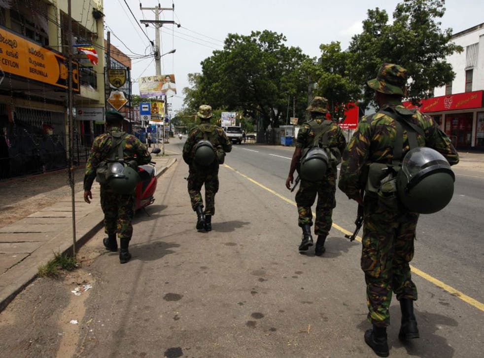 Sri Lanka Police Special Task Force personnel patrol deserted roads following sectarian violence in Aluthgama, 60 kilometers south of Colombo