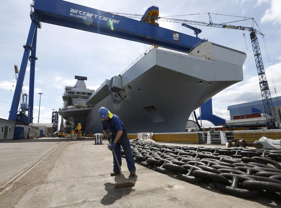 A worker sweeps in front of HMS Queen Elizabeth