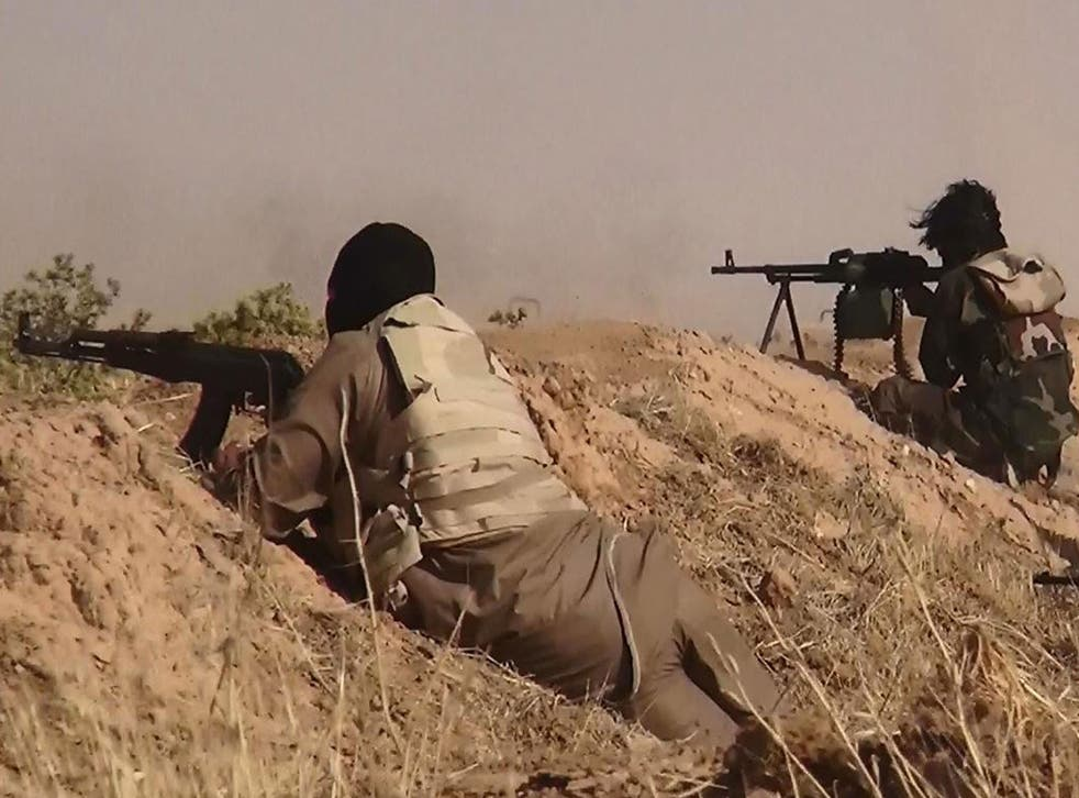 Fighters from the Isis aiming at advancing Iraqi troops at an undisclosed location near the border between Syria and Iraq