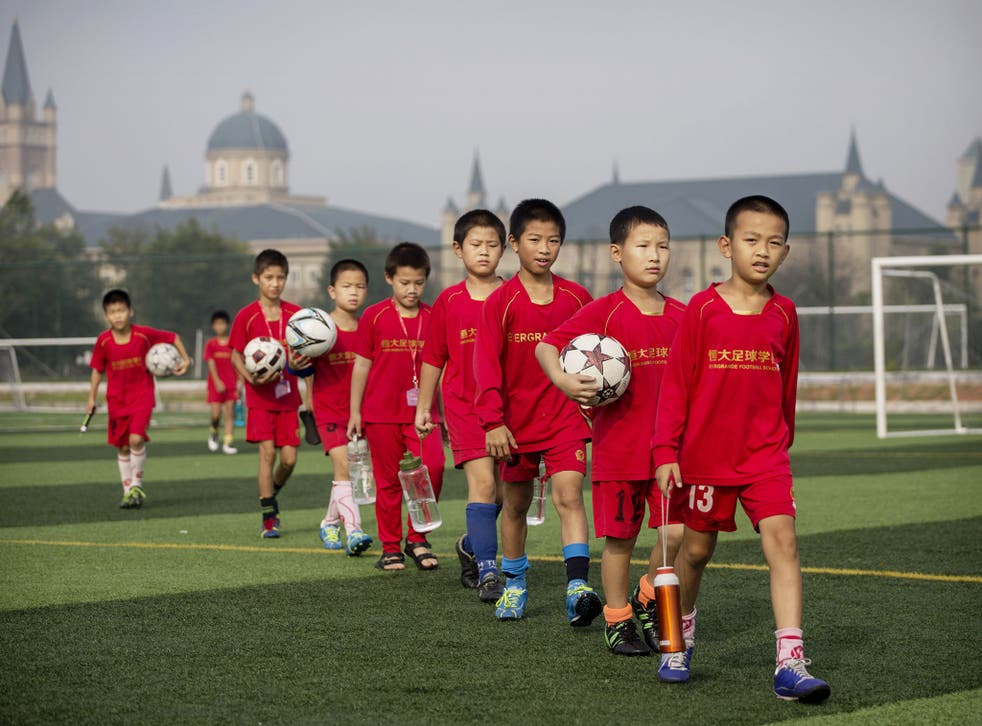 Young Chinese football players walk to training at the Evergrande International Football School near Qingyuan in Guangdong Province