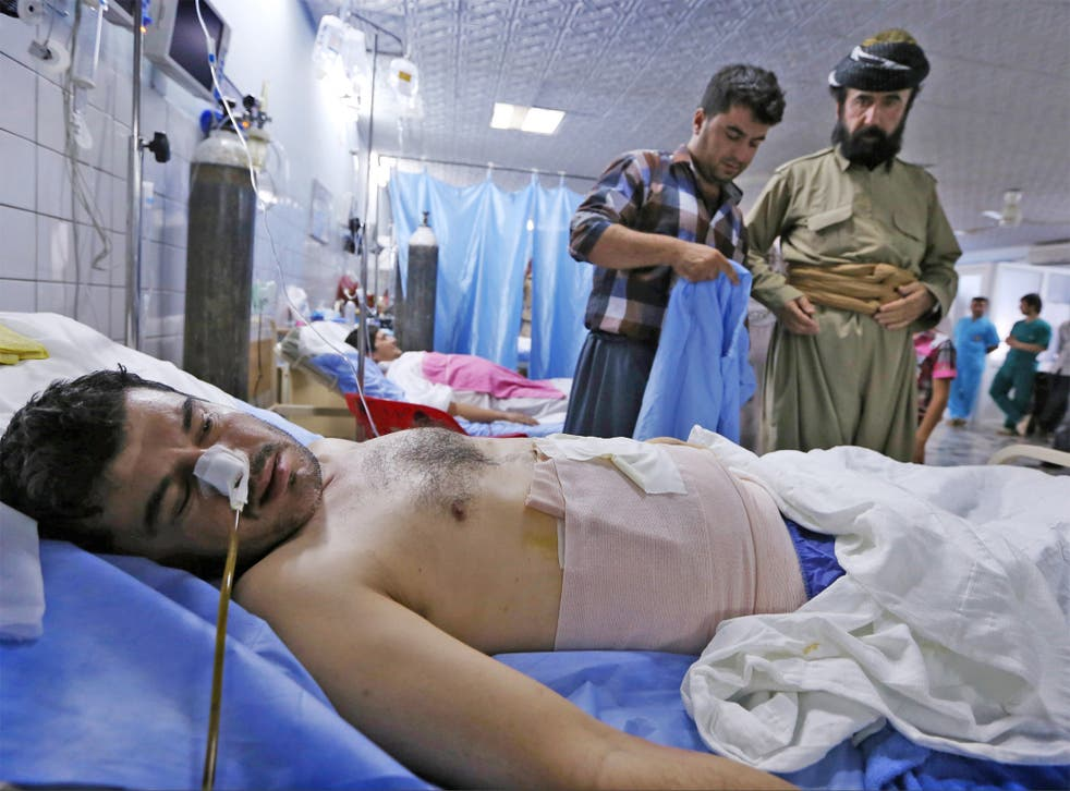 A Kurdish Peshmerga fighter wounded in clashes with ISIL lies on a bed in the emergency ward of a hospital in Arbil