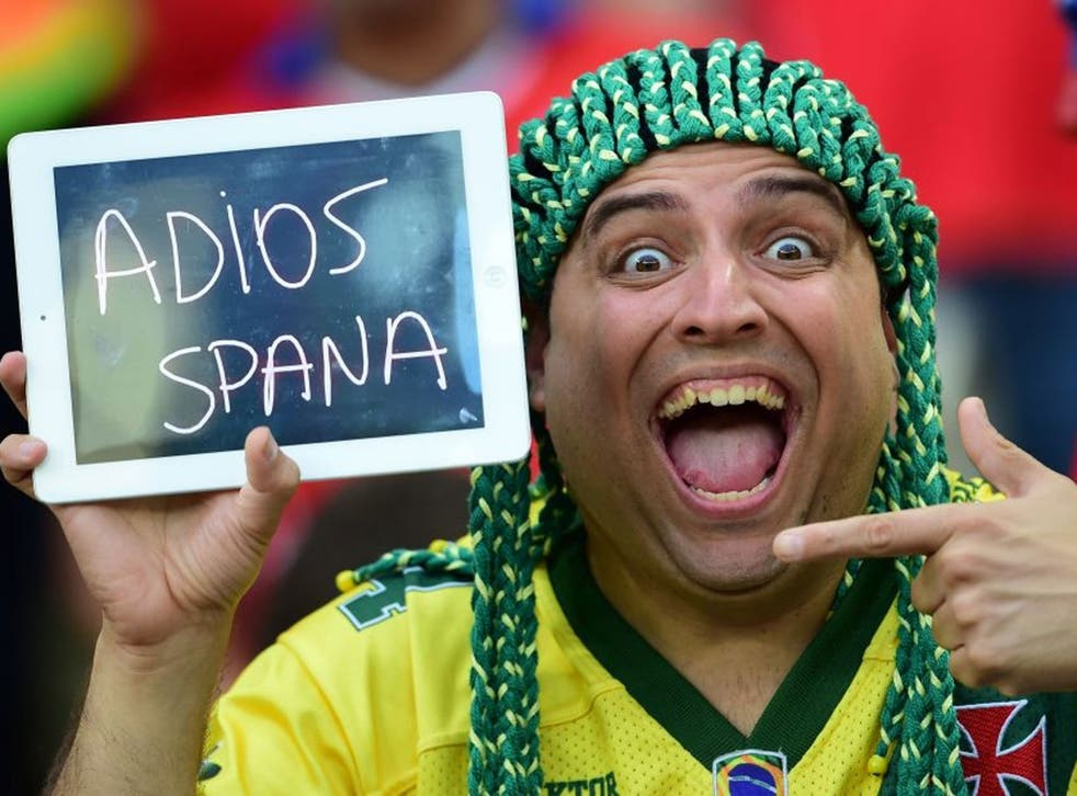 """A Chile fans holds a sign reading in Spanish """"Goodbye Spain"""" after Spain lost their Group B football match against Chile in the Maracana Stadium in Rio de Janeiro during the 2014 FIFA World Cup on June 18, 2014."""