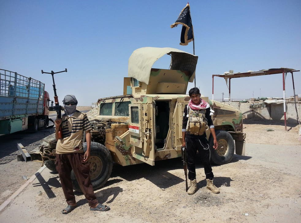 Isis militants with a captured Iraqi army vehicle at a checkpoint outside the Baiji refinery, north of Baghdad, yesterday