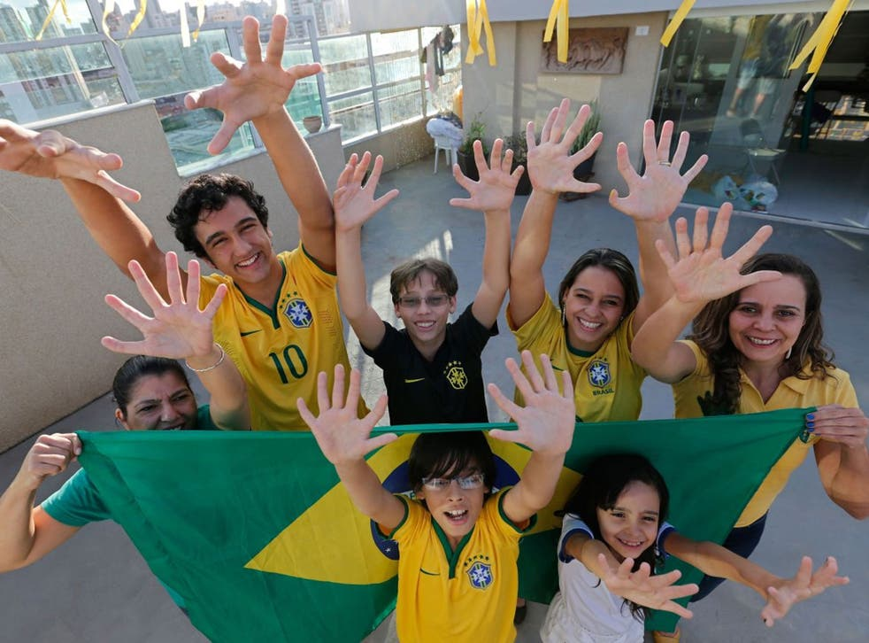 Members of the Silva family, back row, from left, Silvia Santos, Joao de Assis, Pedro de Assis, Ana Carolina Santos and Silvana Santos, front row, Bernardo de Assis, left, and Maria Morena Santos, pose for a photo in their home to show that they each have