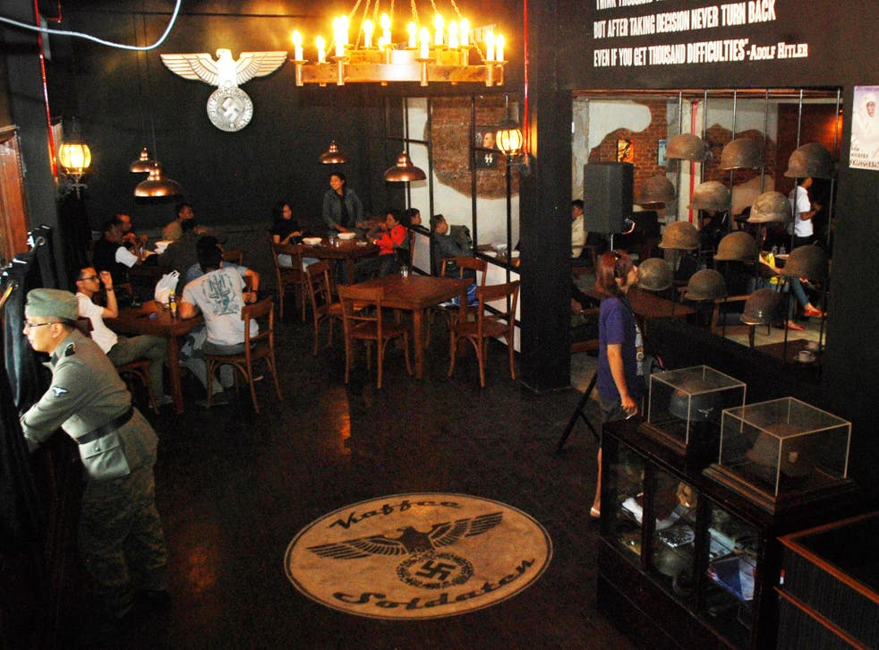 The cafe still features swastikas, Nazi insignia and a painting of Adolf Hitler, as well as a large Nazi emblem on the floor.