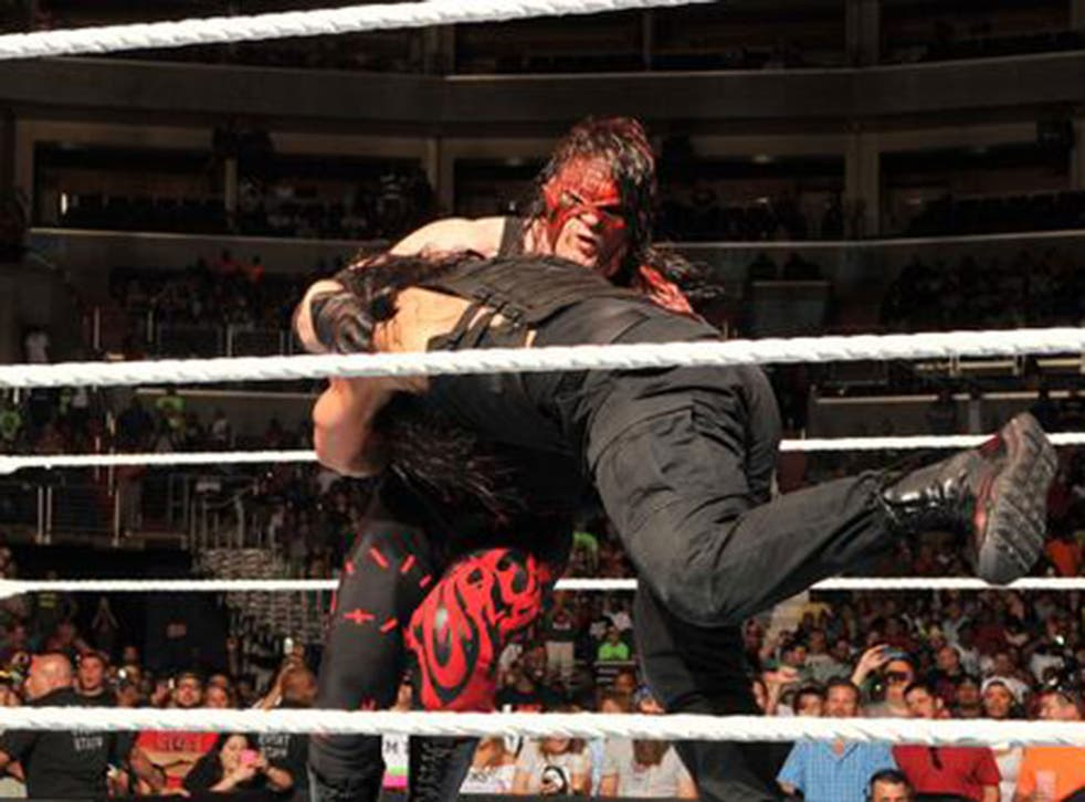 Roman Reigns hits Kane with a spear