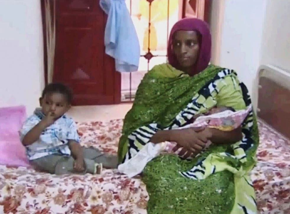 In this file image from an undated video Meriam Ibrahim, sitting next to her 18-month-old son Martin, holds her newborn baby girl as an NGO visits her in a room at a prison in Khartoum