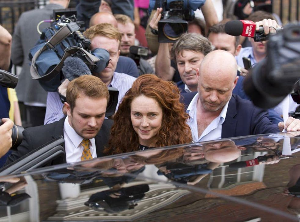 Former News International chief executive Rebekah Brooks is escorted through a crowd of journalists in London with her husband Charlie behind her as she leaves Southwark Crown Court having been found not guilty on all charges