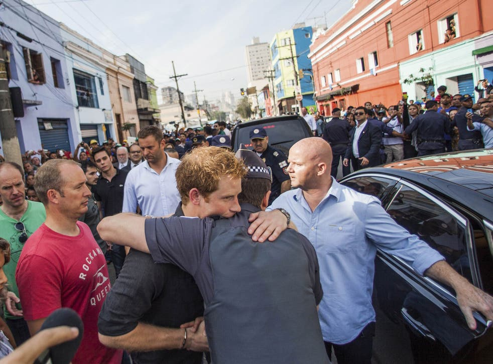 Prince Harry (C) embraces a resident during a visit to Sao Paulo's Luz neighborhood known to locals as Cracolandia (Crackland)