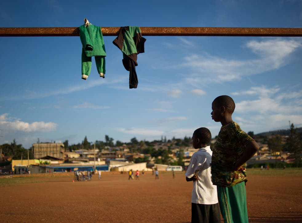 Rwandan youths watch a football game on March 16, 2014 at Gikondo suburb in the capital, Kigali.
