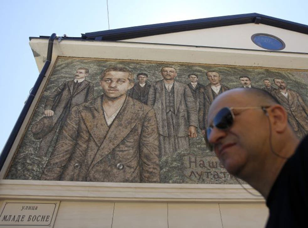 A man walks by a mosaic depicting assassin Gavrilo Princip, in Visegrad