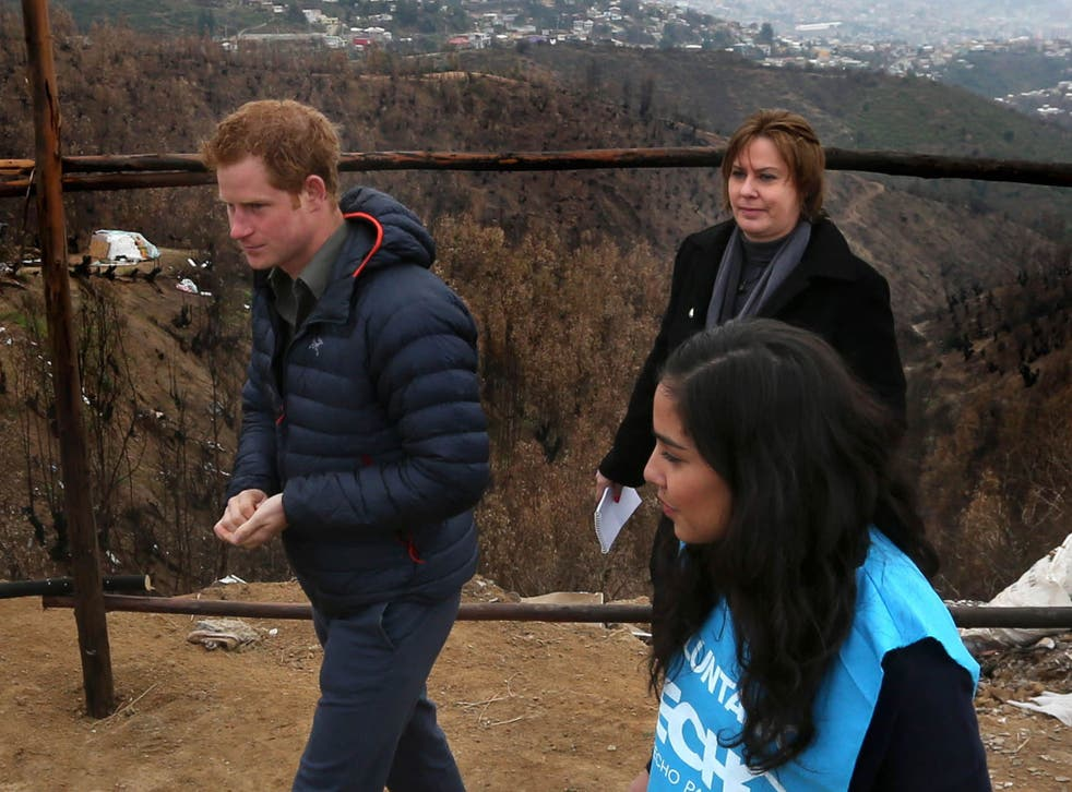 Prince Harry is shown the devastation left by the Valparaiso fire that burnt down many homes in the poorest area of the town