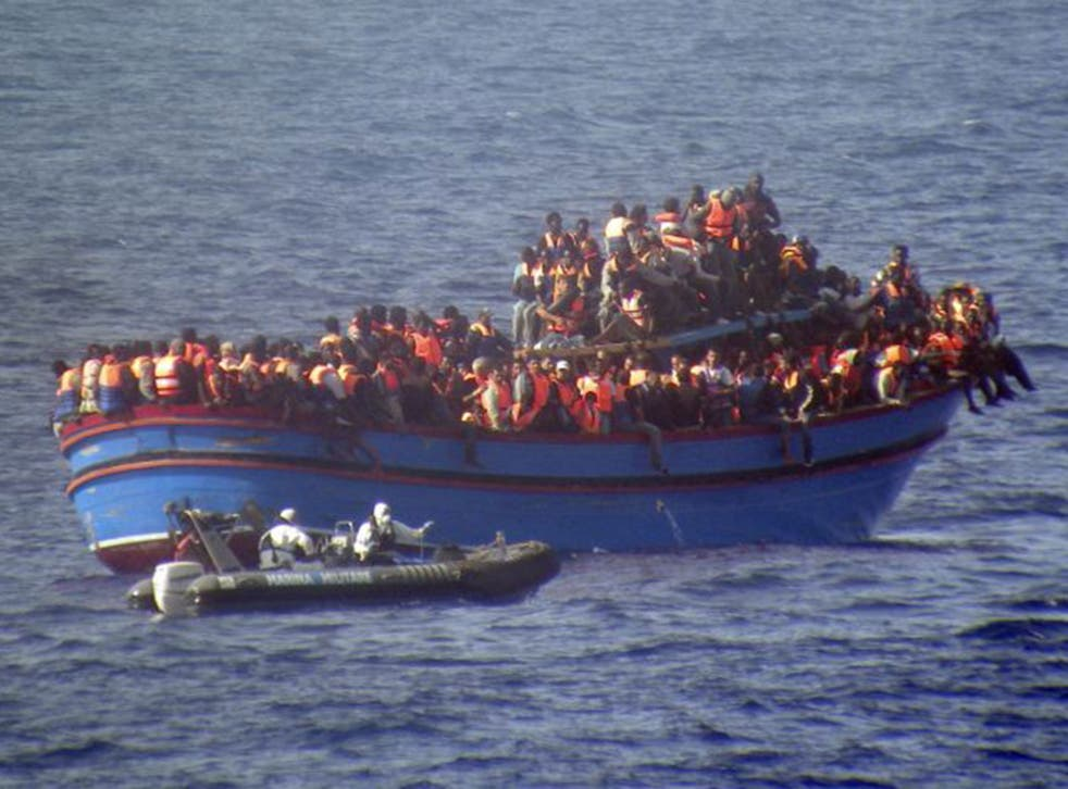 An Italian navy motor boat approaches a boat full of migrants making its way to Europe. The boat was carrying almost 600 people – but some 30 died during the journey