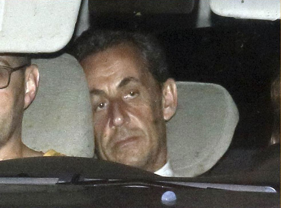 Nicolas Sarkozy arrives with police by car at the financial investigation unit in Paris to be presented to a judge