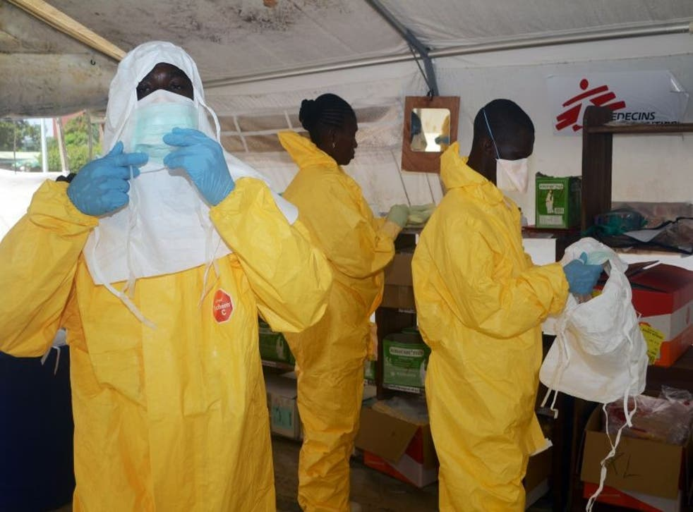 Members of Doctors Without Borders (MSF) put on protective gear at the isolation ward of the Donka Hospital in Conakry, where people infected with the Ebola virus are being treated.
