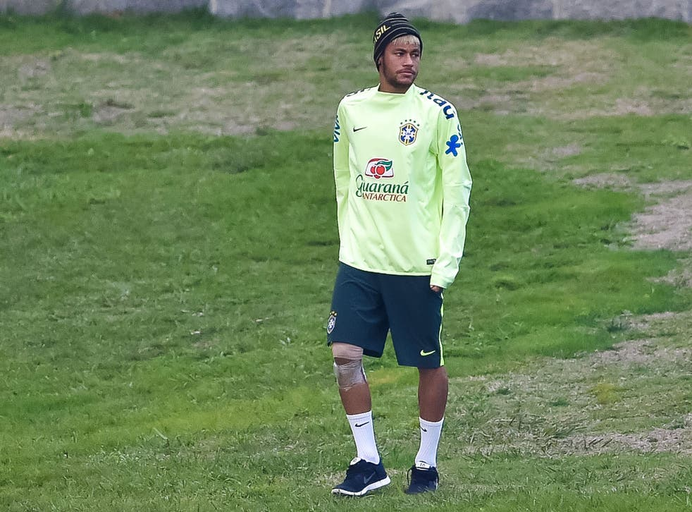 Neymar attends a Brazil training session with him right knee strapped up