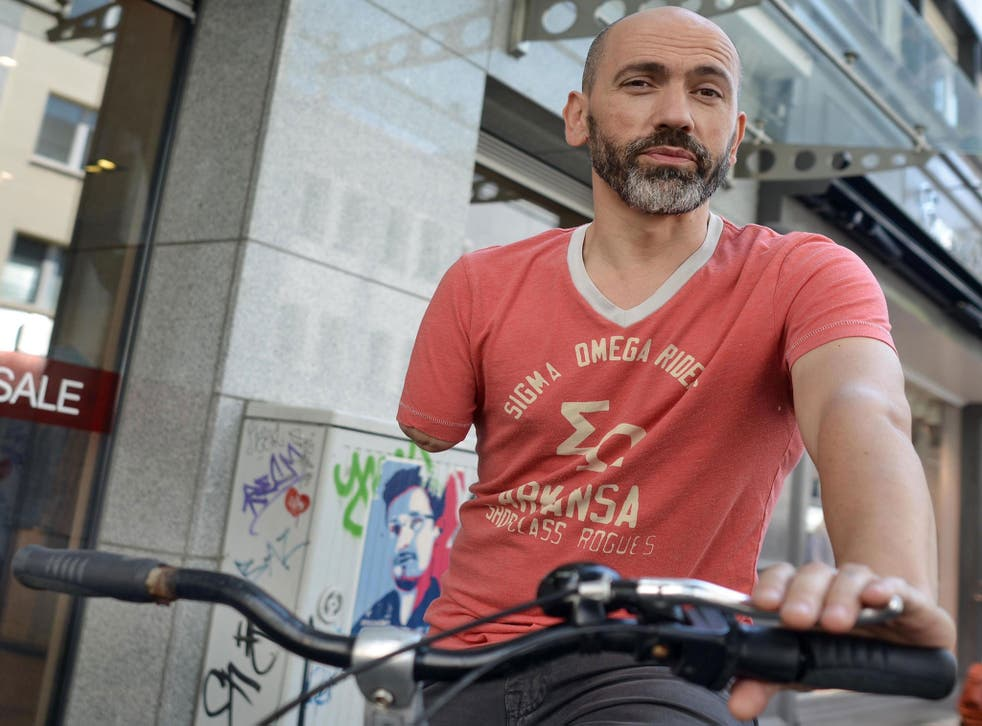 One-armed cyclist Bogdan Ionescu poses with his bike on July 1, 2014 in Cologne, western Germany