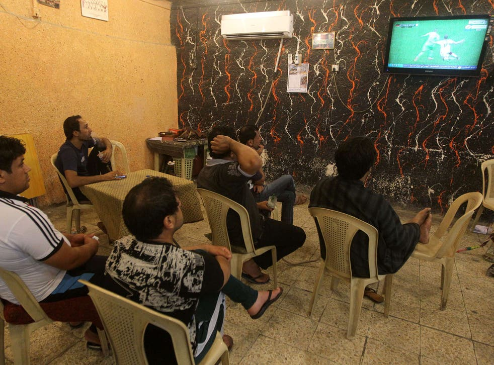 """Iraqi Raad Abdulhussein (centre) and his friends sit watching on the World Cup match between Algeria and Germany at the """"Facebook"""" cafe in the Iraqi capital Baghdad"""