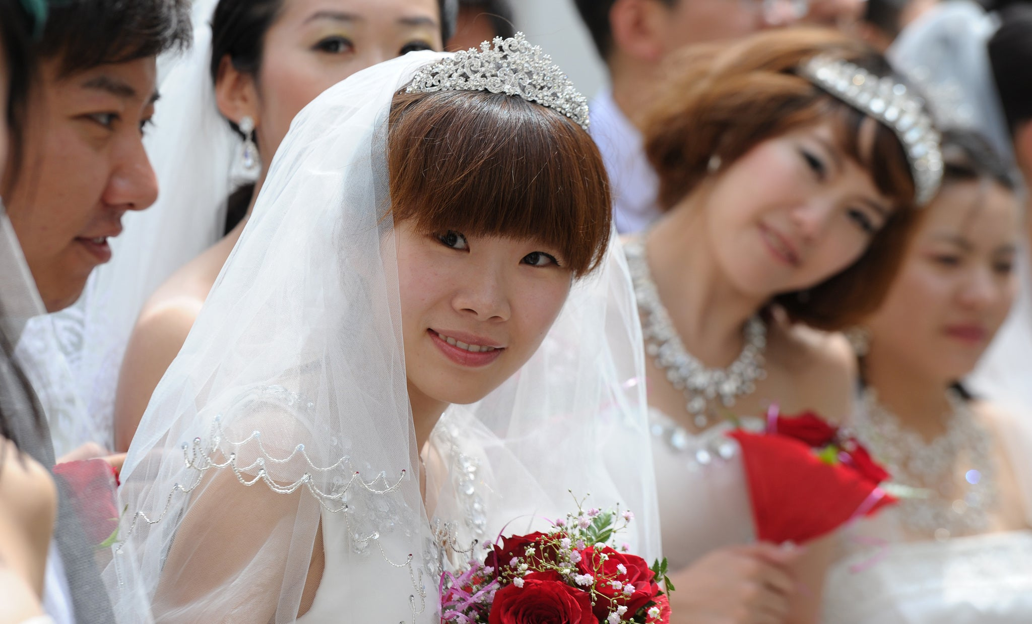 Thousands of female graduates across China ditch the mortar board for wedding dresses
