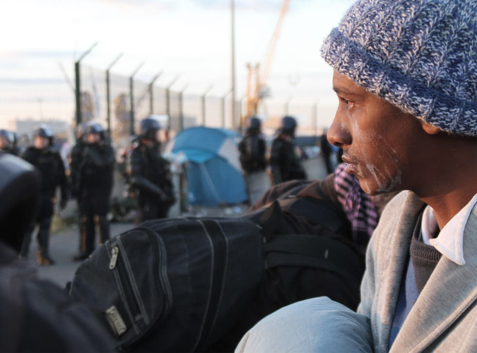 A migrant, his face streaked with the after-effects of tear gas, awaits transportation to a detention centre following the clearance of a camp in Calais