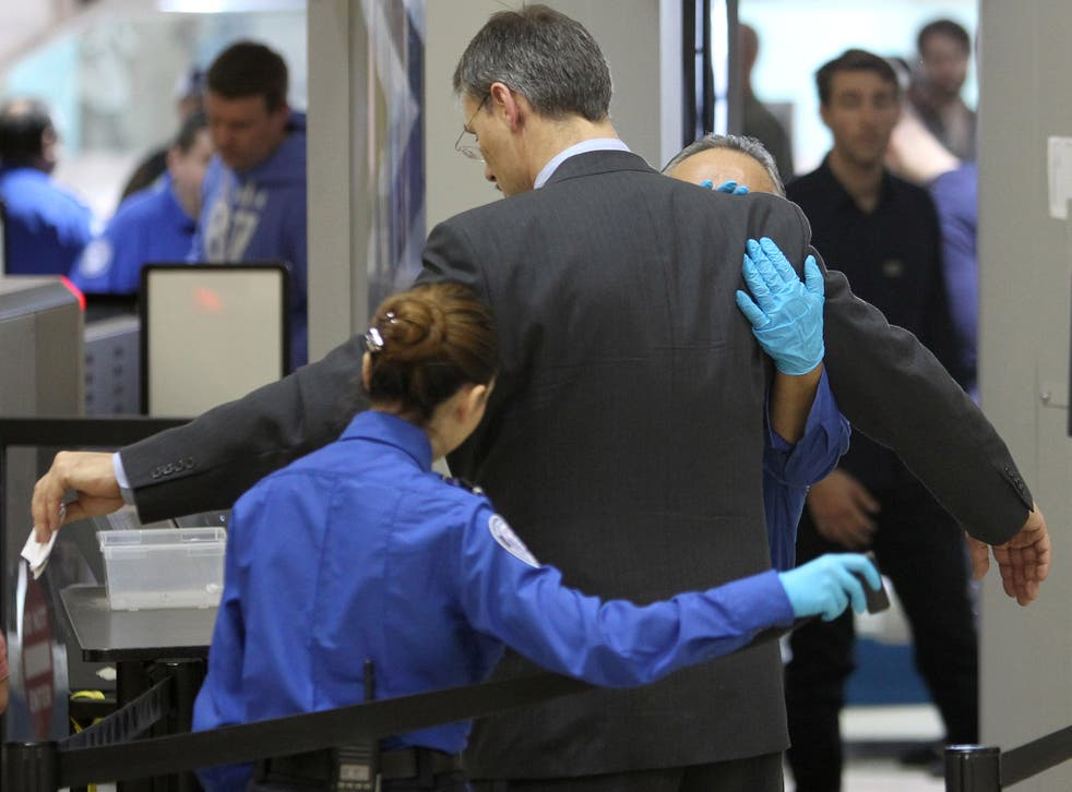 A plane passenger is patted down after passing through a full-body scanner at Los Angeles International Airport
