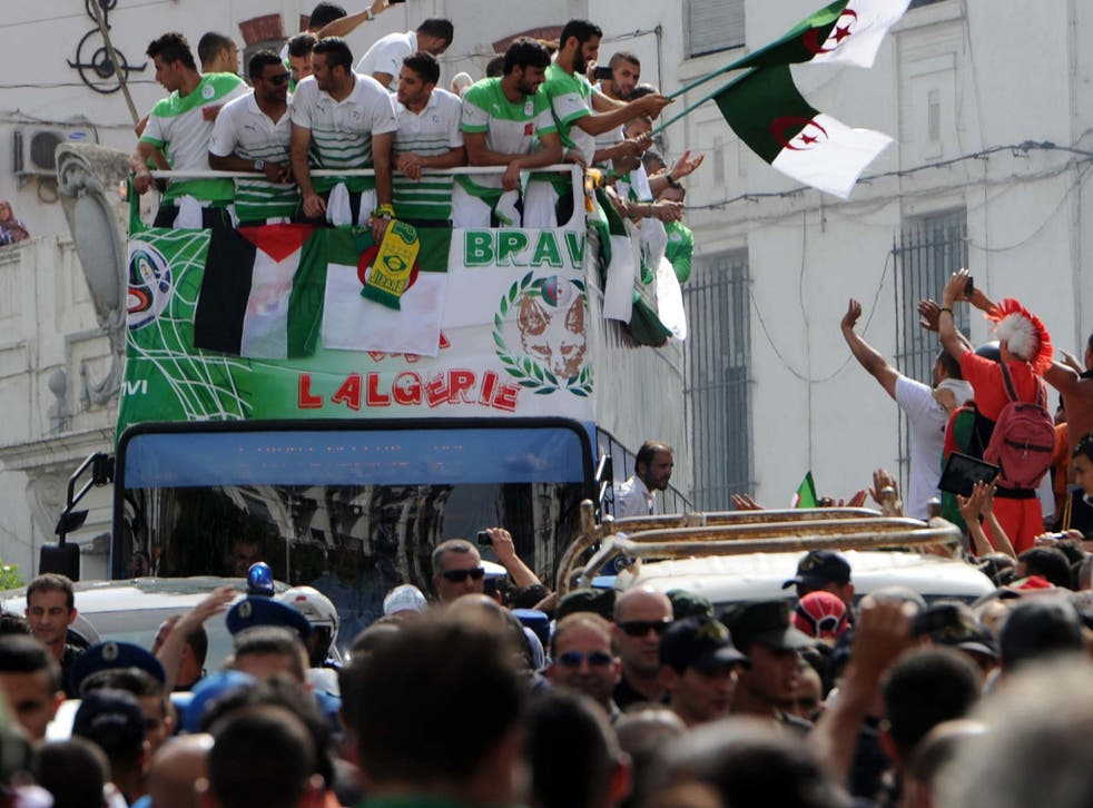 The Algeria World Cup team on their open-bus tour through Algiers. A Palestinian flag can be seen draped from the front of the bus