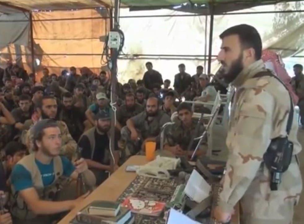 Zahran Alloush, the military leader of the Islamic Front, talking to militants near Damascus