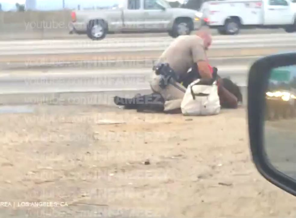 The footage appears to show the officer punching the woman while she is on the floor