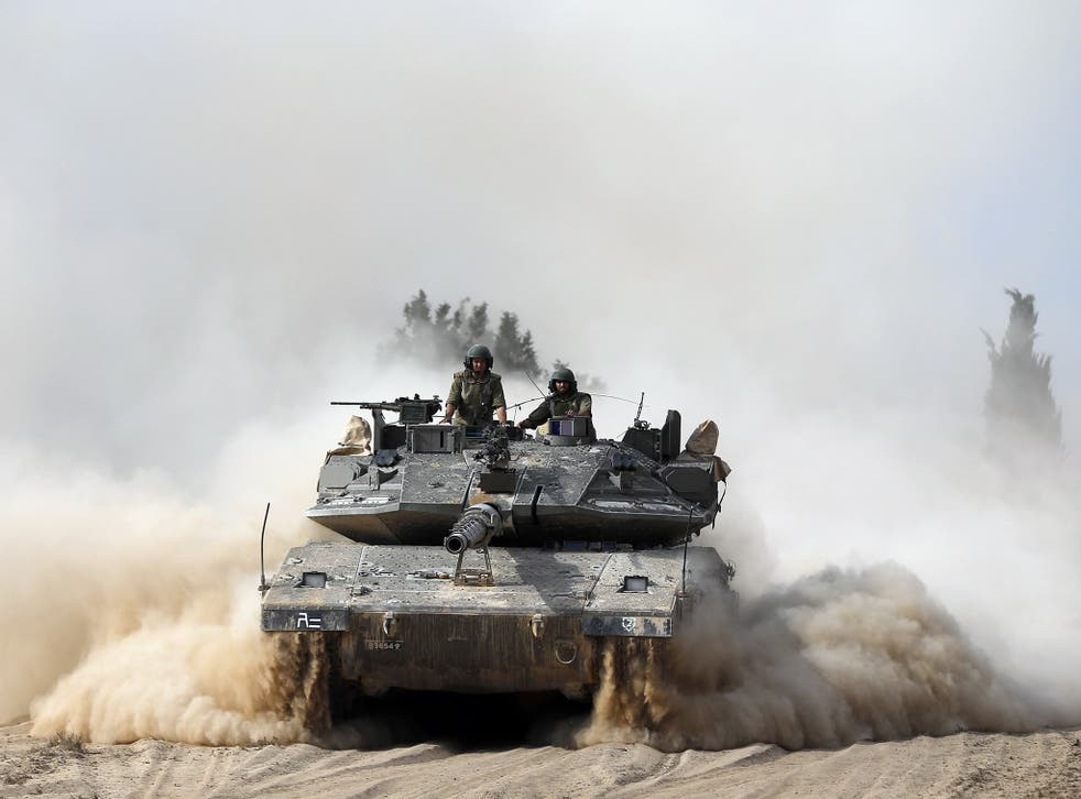 Israeli soldiers ride atop a tank outside the southern Gaza Strip.