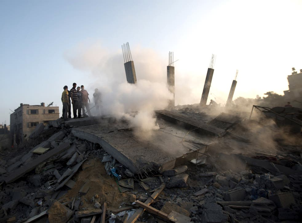 Palestinians walk over the rubble of a building destroyed by an Israeli air strike on Gaza City
