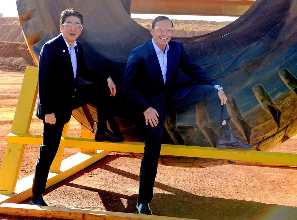 Australian Prime Minister Tony Abbott (R) and Japanese Prime Minister Shinzo Abe pose for a photograph next to a haulage truck tyre during a tour of Rio Tinto's West Angelas iron ore mine in Pilbara, Western Australia on July 9, 2014