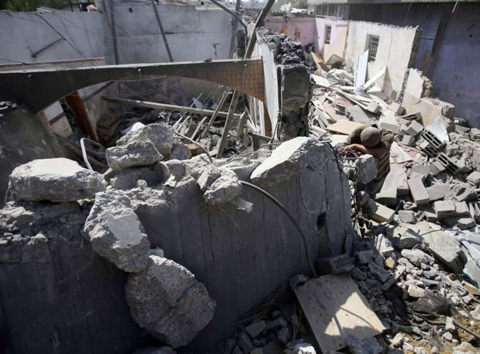 A Palestinian man leans over the rubble of his house which police said was destroyed in an Israeli air strike in Khan Younis in the southern Gaza Strip July 10, 2014. At least 74 Palestinians, most of them civilians, have been killed in Israel's Gaza offe