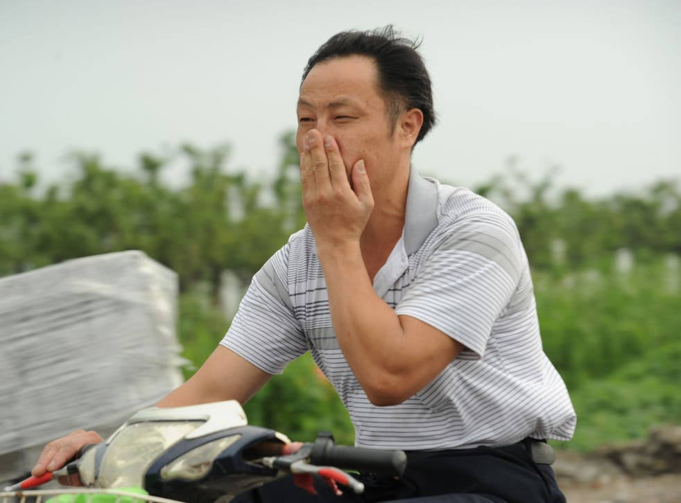 A man, unrelated to the study, on his motorcycle covers his nose against a bad smell