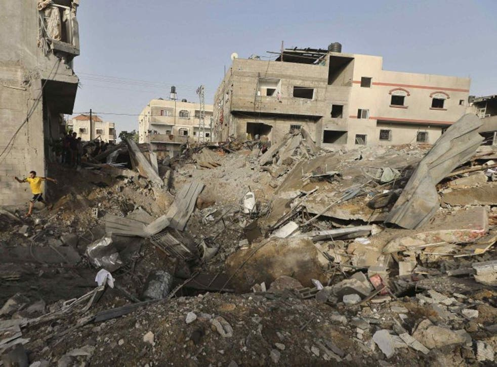 A Palestinian man walks amidst the rubble of a house which police said was destroyed in an Israeli air strike in the northern Gaza Strip July 12, 2014.