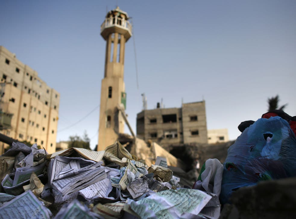 Damaged copies of Islam's holy book the Koran lie on the rubble from a destroyed mosque following an Israeli military strike in the Nusseirat refugee camp in the central Gaza Strip