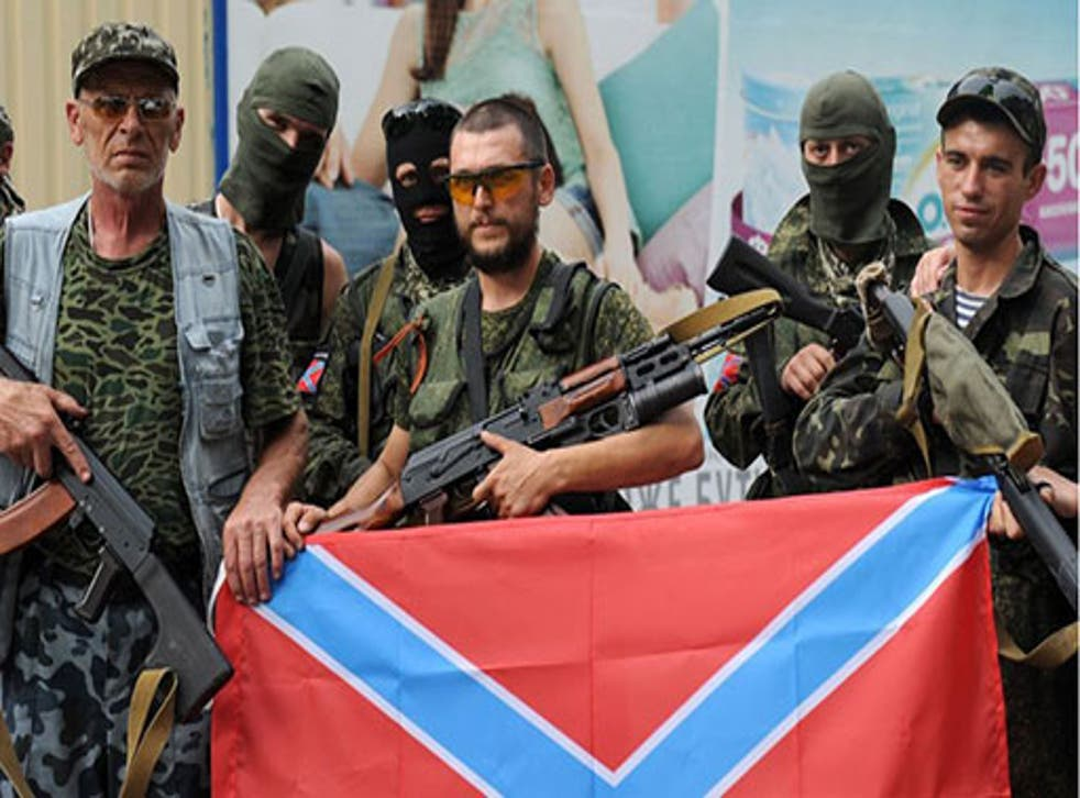 Pro-Russian militants pose on July 13, 2014 with the new Russia flag in Donetsk, eastern Ukraine