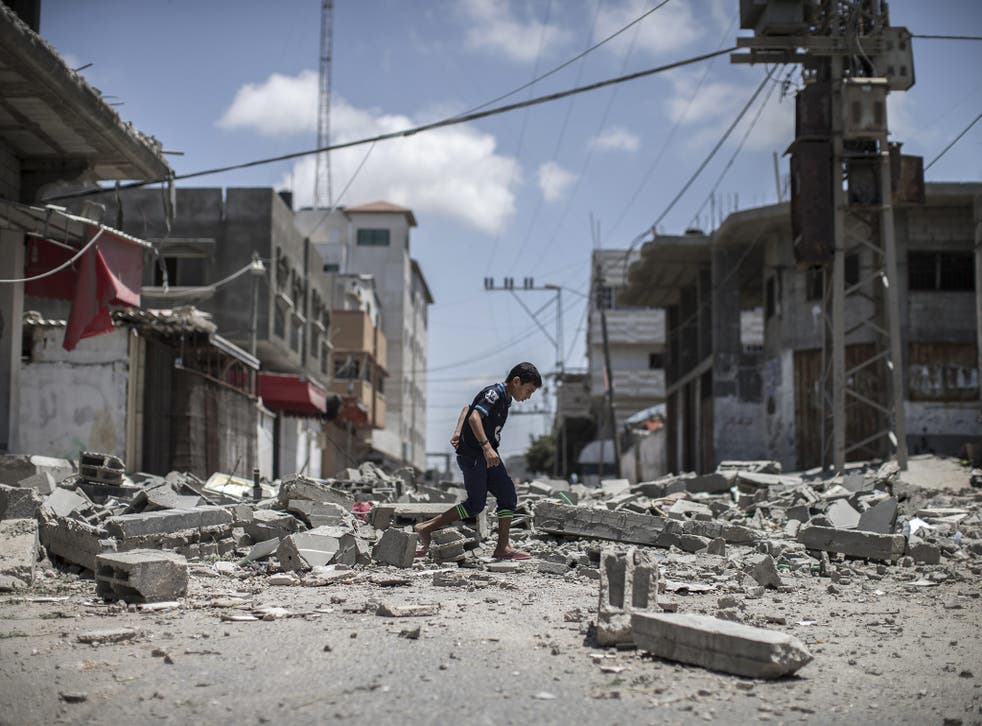 A young Palestinian boy walks over debris from a house that was destroyed in an airstrike in Deir Al Balah