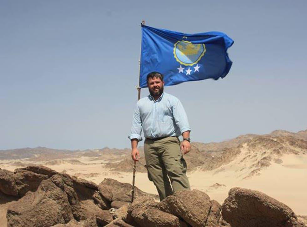 Jeramiah Heaton putting up a flag to make his daughter Princess of the Kingdom of North Sudan