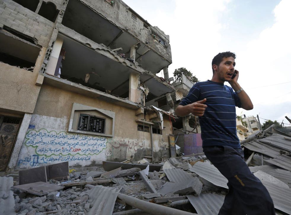 A Palestinian talks on a mobile phone as he walks on the rubble of a damaged house following an overnight Israeli missile strike in Gaza City, Tuesday, July 15, 2014