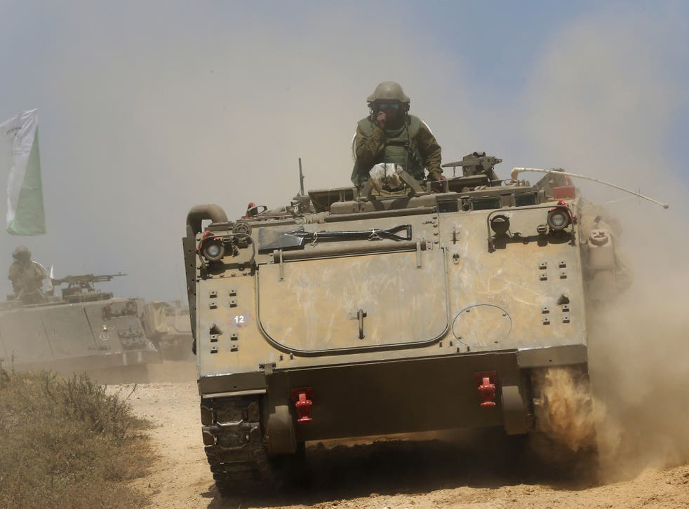 Israeli soldiers on armored personnel carriers move to a new position on the Israel-Gaza Border