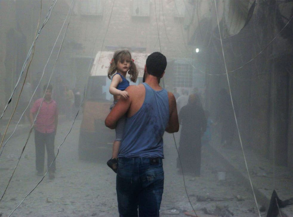 A Syrian man carries a girl on a street covered with dust following an air strike by government forces in the northern city of Aleppo
