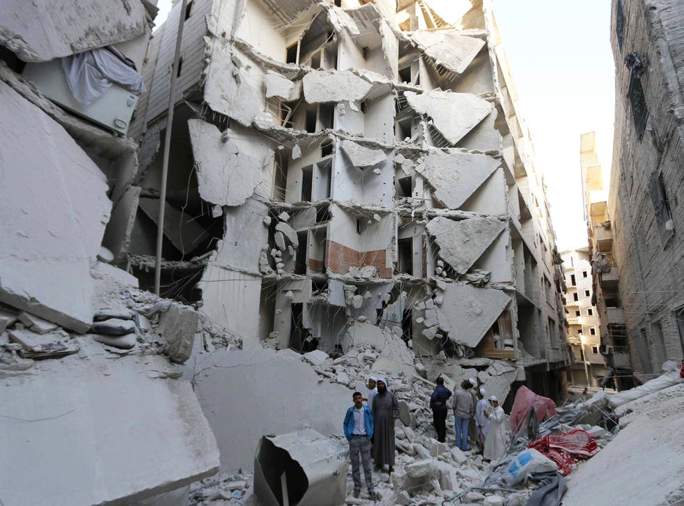 People stand on the rubble of collapsed buildings at a site hit by what activists said was a barrel bomb dropped by forces loyal to Syria's President Bashar al-Assad, in the Al-Fardous neighbourhood of Aleppo