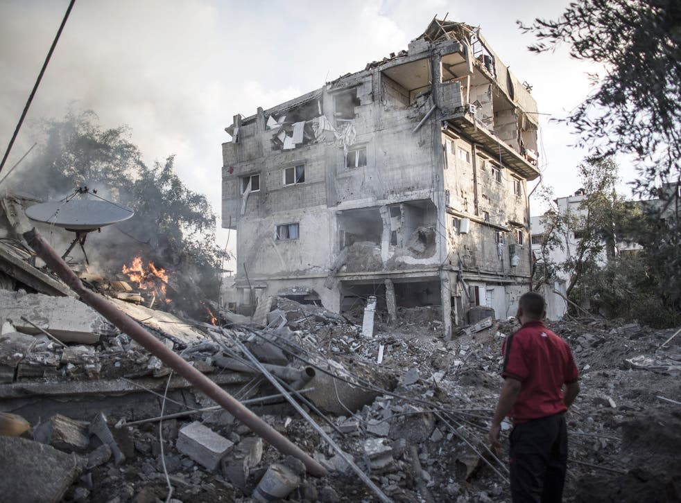 A Palestinian man looks at a house destroyed by Israeli Defense Forces during an overnight air strike in Gaza City