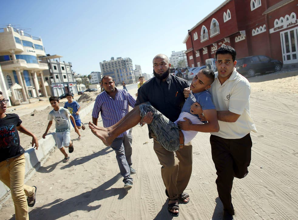 Palestinian employees of Gaza City's al-Deira hotel carry a wounded boy following an Israeli military strike nearby on the beach