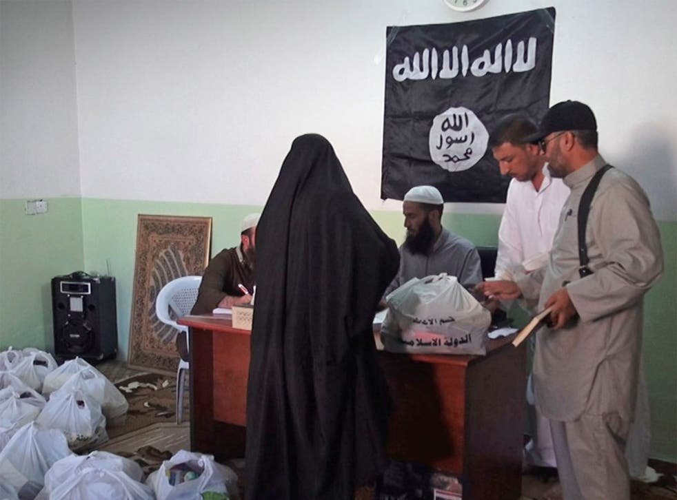A woman collecting aid administered by Isis in Syria