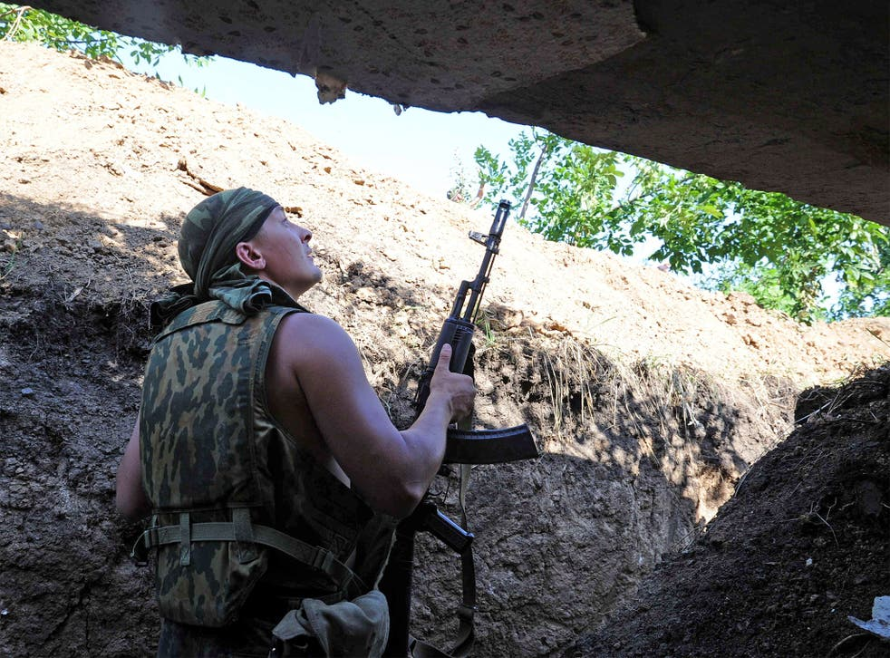 A pro-Russia militant stands in a trench as he takes shelter from bombing by a Ukrainian army plane near the town of Marynivka, 100 km east of Donetsk